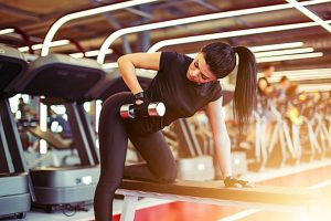 woman using bench for dumbbell row