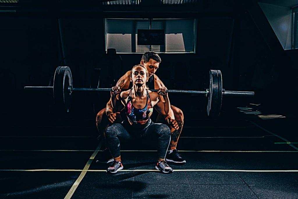 woman squatting with man spotting