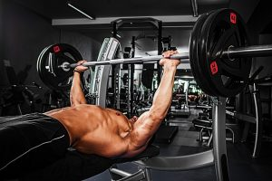 man on olympic weight bench in gym